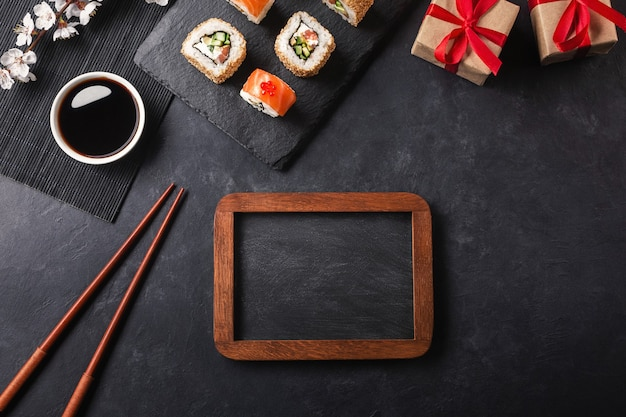 Set of sushi and maki rolls, gift boxes with branch of white flowers and chalk board on stone table. top view with place for your text.