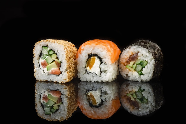 Set of sushi and maki rolls on the glass table with reflection