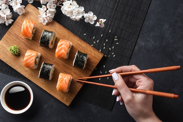 Set of sushi, maki rolls, hand with chopsticks and branch of white flowers on stone table. top view.