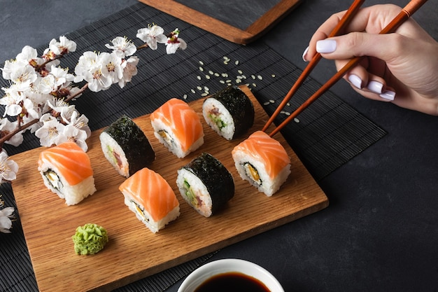 Set of sushi and maki rolls, hand with chopsticks and branch of white flowers on stone table. top view.