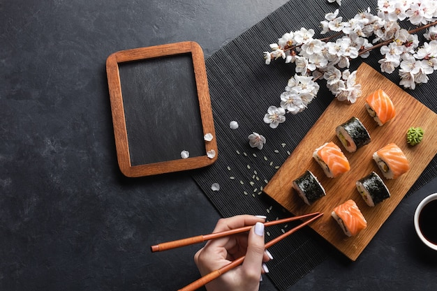Set of sushi and maki rolls, hand with chopsticks, chalk board and branch of white flowers on stone table. top view.