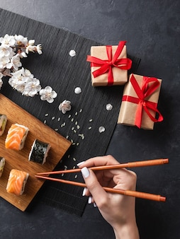 Set of sushi and maki rolls, hand with chopsticks, gift boxes and branch of white flowers on stone table. top view.