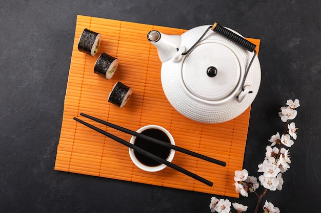 Set of sushi and maki rolls with branch of  teapot with the inscription green tea on stone table.