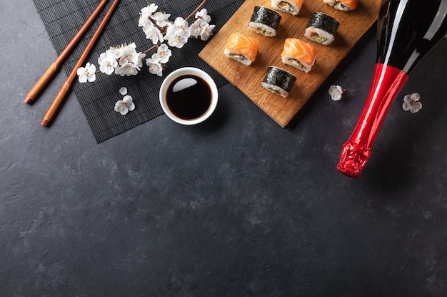Set of sushi and maki rolls with branch of white flowers and bottle of champagne on stone table. top view.