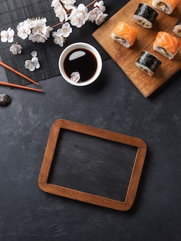 Set of sushi and maki rolls with branch of white flowers and chalk board on stone table. top view with place for your text.