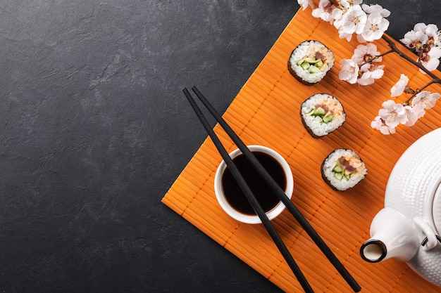 Set of sushi and maki rolls with branch of white flowers on stone table. top view.