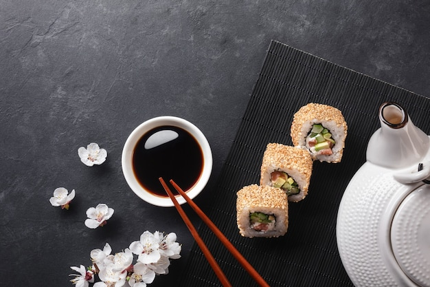 Set of sushi and maki rolls with branch of white flowers and teapot on stone table. top view.