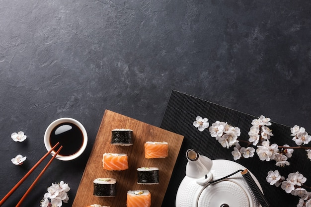 Set of sushi and maki rolls with branch of white flowers and teapot with the inscription green tea on stone table. top view.