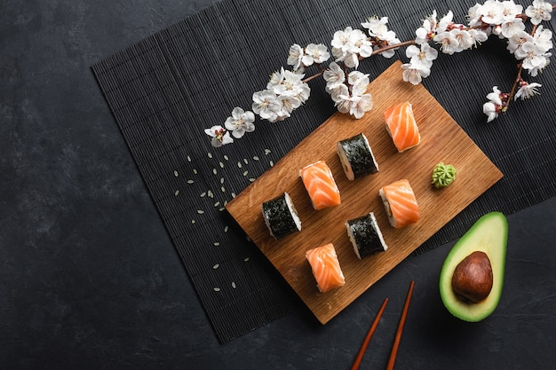 Set of sushi and maki rolls with sliced avocado and branch of white flowers on stone table. top view.