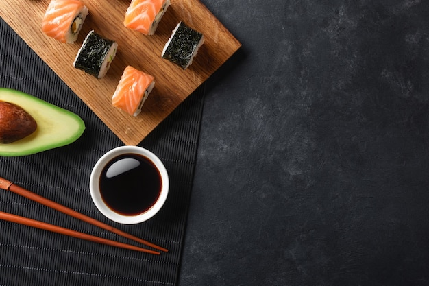 Set of sushi and maki rolls with sliced avocado on stone table. top view.