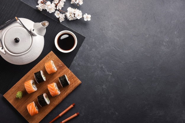 Set of sushi and maki rolls with of teapot  green tea on stone table.