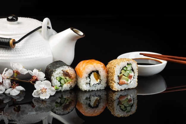 Set of sushi and maki rolls with white teapot on the glass table with reflection