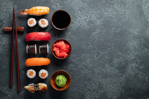 Set of sushi and maki on stone table.