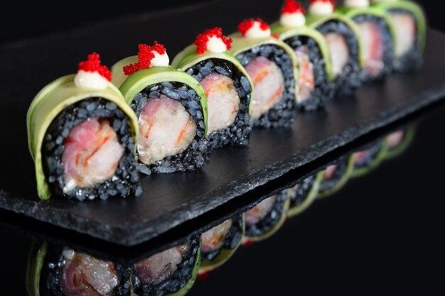 Set of sushi rolls on black desk background
