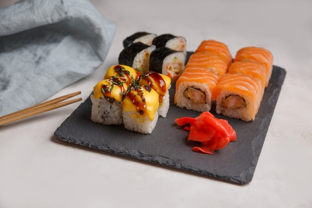 Set of sushi rolls on a black stone board. grey surface