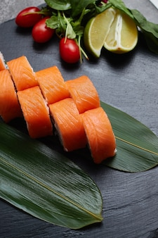 Set of sushi rolls lies on bamboo leaves with lime, herbs and red tomatoes, served on a black stone slate.