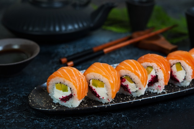 A set of sushi rolls philadelphia with red fish and cream cheese lies in a plate boat. sushi rolls on a black background with a teapot of chinese tea. close up.