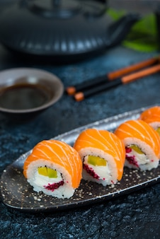 A set of sushi rolls philadelphia with red fish and cream cheese lies in a plate boat. sushi rolls on a black background with a teapot of chinese tea. close up