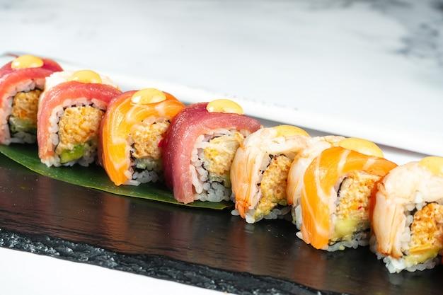 젓가락과 간장 대리석 테이블에 검은 돌에 바나나 잎에 제공되는 스시 롤을 설정합니다. 일본 음식. 연어와 참치 새우 초밥. 건강한 해산물.