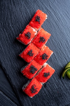 Set of sushi rolls with cream cheese, rice and salmon on a black board decorated with ginger and wassabi on a dark wooden table. japanese cuisine. food photo table. top view