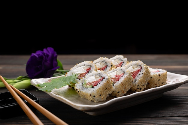 Set of sushi rolls with cream cheese rice and salmon on a board decorated with ginger on a wood