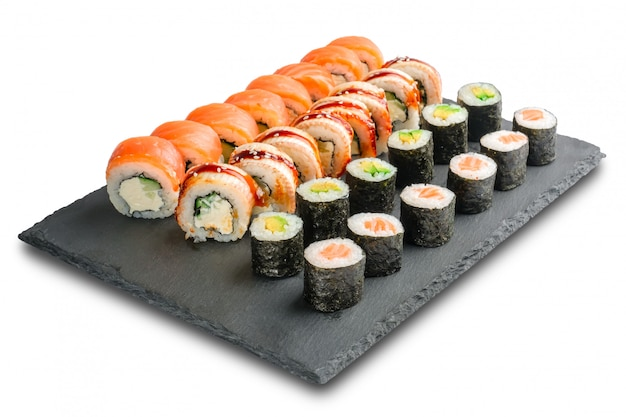 Set sushi rolls with eel, salmon, avocado, cucumber, nori leaves and cream cheese inside isolated on white