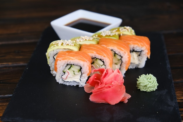 Set of sushi rolls with tuna, salmon, cucumber, avocado on a black table. close-up, shallow depth of field. assortment of japanese food in restaurant.