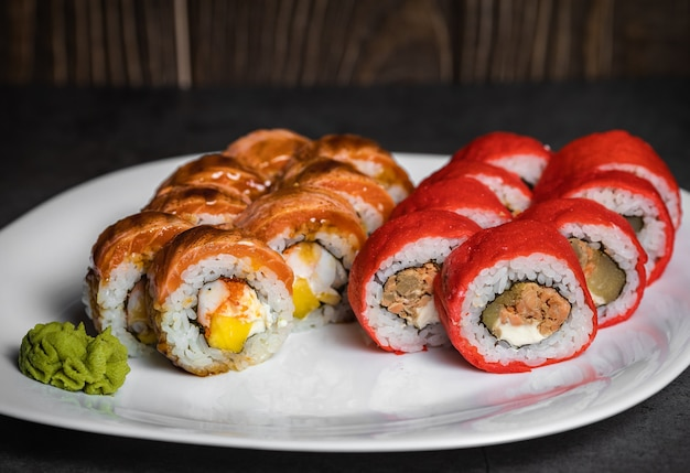 Set of sushi rolls with wasabi cheese and ginger and salmon on a white plate
