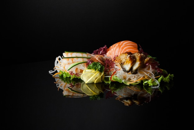 A set of sushi with shrimps on a black background with reflection
