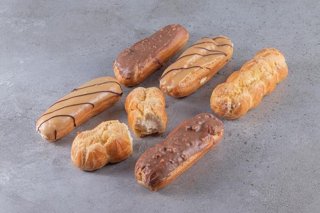 Set di bignè dolci con vari ripieni sulla superficie della pietra