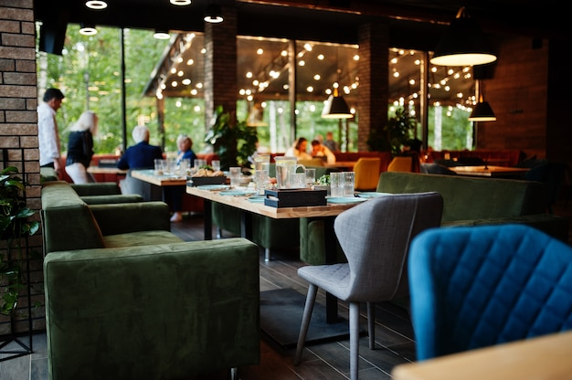 아늑한 인테리어, 안경, 포크, 나이프가 저녁 식사로 제공되는 레스토랑에서 테이블을 설정하십시오.