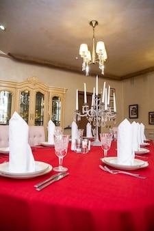 빨간 식탁보와 가전제품으로 식당에 테이블을 놓으십시오.