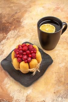 Apparecchia la tavola con una torta regalo e il tè in una tazza nera con il limone sulla tavola dei colori misti
