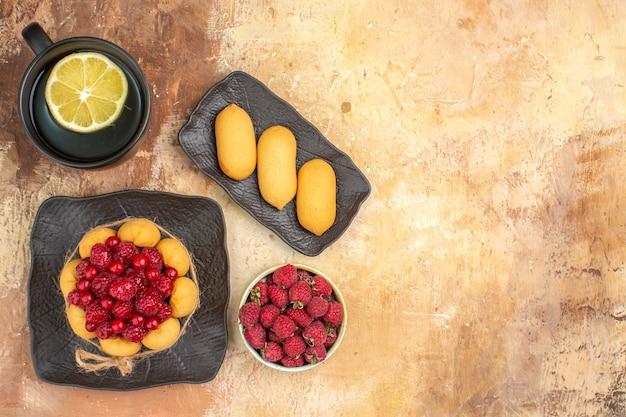 Apparecchiare la tavola con una torta regalo con lamponi e una tazza di tè al limone su un tavolo a colori misti