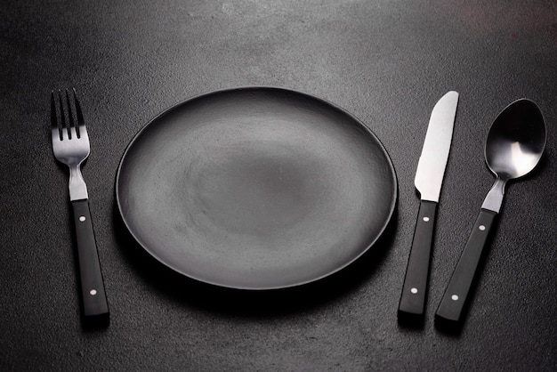 Set of tableware ready for the meal with black copy space. metal knife, fork, spoon and plate