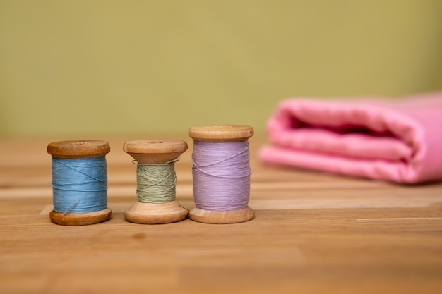 Set of tailoring accessories. close up of a stack of folded pink fabric, sewing scissors, and spools of thread
