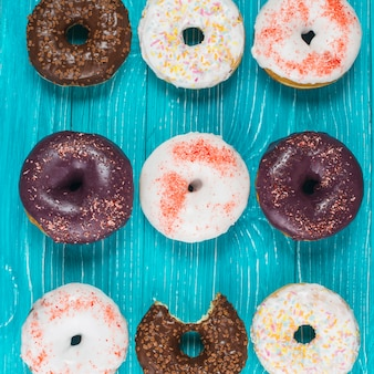 Set of tasty bitten doughnuts with chocolate coating and sprinkles