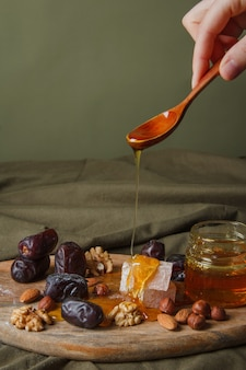 Set for tea drinking. hand holding spoon with dripping honey. various sweets, nuts and honey for tea on a wooden cutting board. healthy sweets, delicious dessert, natural sweets.