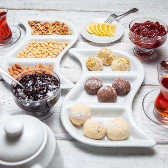 Set di tè, noci, fette di limone, teiera, marmellata di frutta e deliziosi dessert su un fondo di legno bianco. veduta dall'alto.