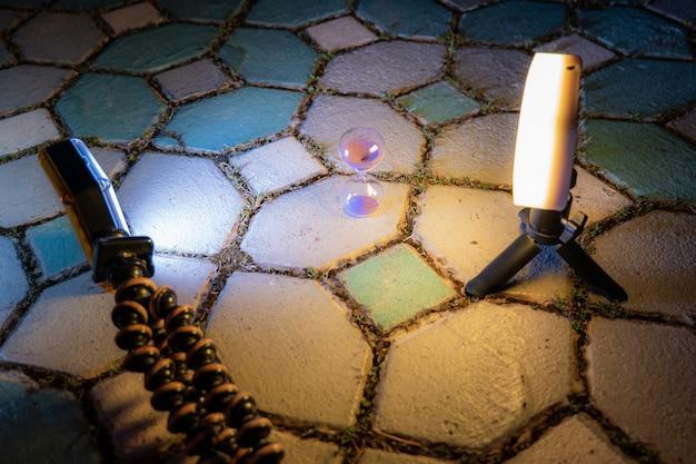 Установите свет, поставьте песочные часы вне места, когда свет тусклый. Premium Фотографии