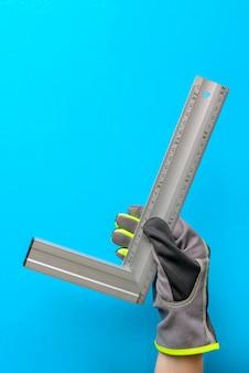 正方形を設定します。建設テーマバナー。手袋をはめた手の角度を測定するための構造測定装置。建設と生産のコンセプト。