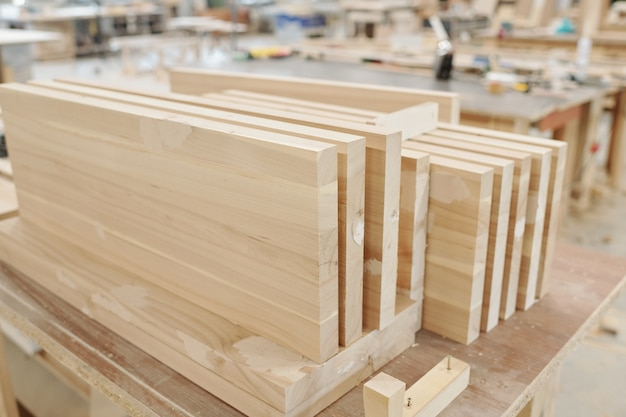 Set of thick large wooden boards or workpieces for production of furniture on workbench of engineer inside workshop of modern factory
