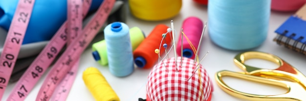 Set of threads and needles lying at worktable