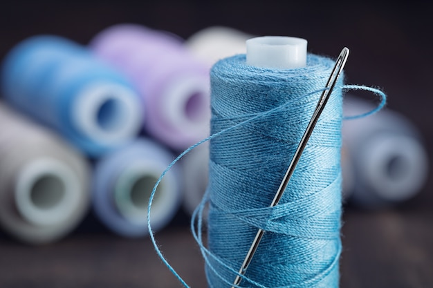 Set of threads of pastel tones on reels, in foreground coil of blue threads with large needle.