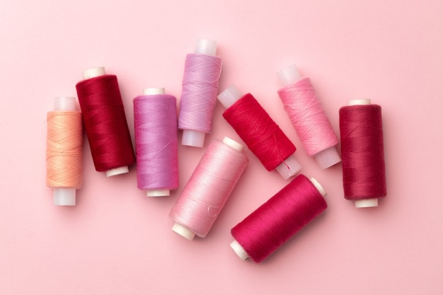 Set of threads spools on pink background