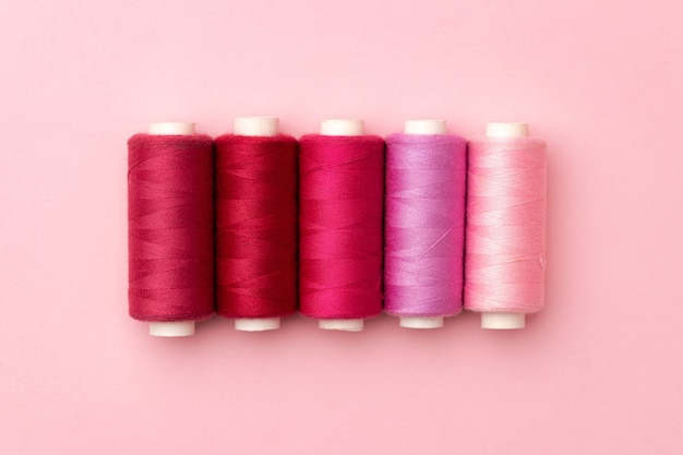 Set of threads spools on pink