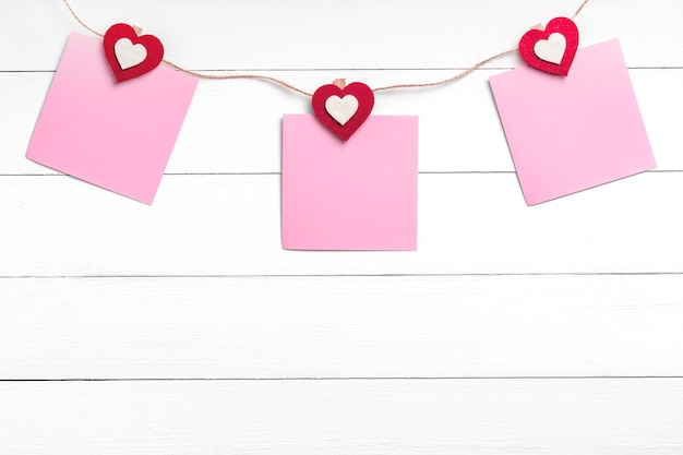 Set of three blank stickers hanging on string with clothespins behind white wooden surface.  paper notes held on rope with red hearts. copy space, top view.