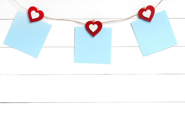 Set of three blank stickers hanging on string with clothespins behind white wooden surface.