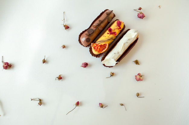 Set of three eclairs with different fillings and design. isolate on a white surface decorated with dry roses