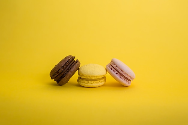 Set of three macarons on a yellow space with copy space. brown, yellow and pink macaroni are in a row.